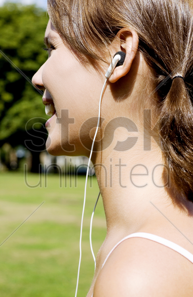 woman listening to music while jogging in the park stock photo
