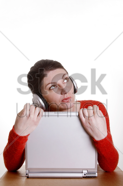 woman listening to music while using laptop stock photo