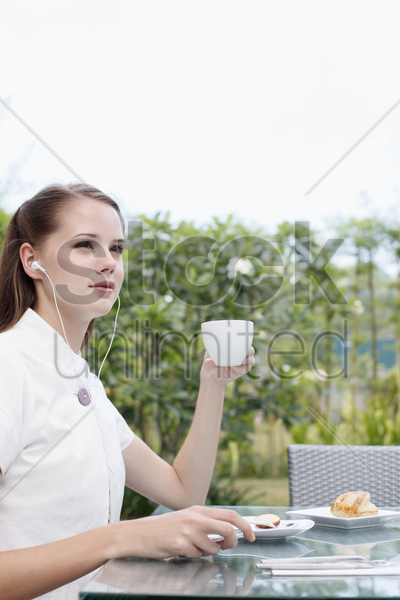 woman listening to portable mp3 player while having coffee stock photo
