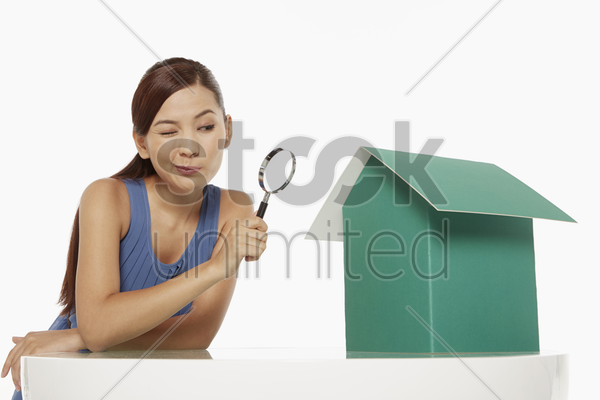 woman looking at a cardboard house with magnifying glass stock photo