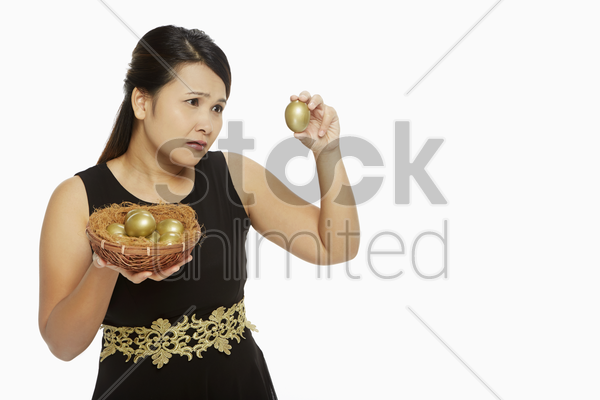 woman looking at a golden egg with curiosity stock photo