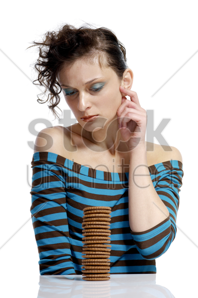 woman looking at a stack of biscuits stock photo