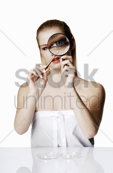 woman looking at a tiny object with a magnifying glass stock photo
