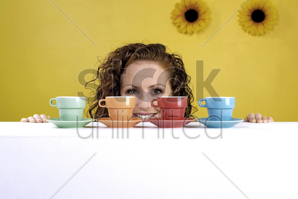 woman looking at an arrangement of cups and saucers stock photo