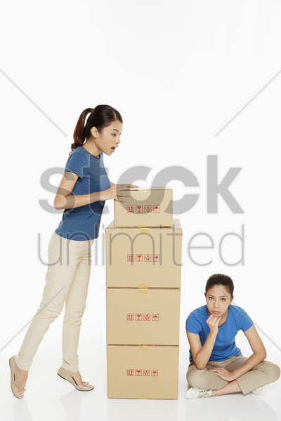 woman looking at another woman sitting on the floor stock photo
