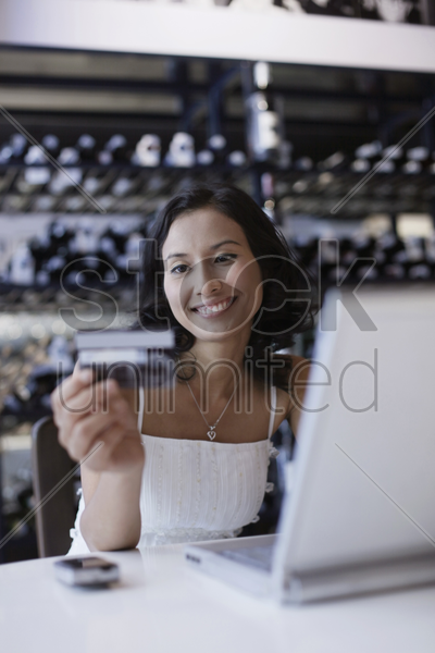 woman looking at credit card while using laptop stock photo