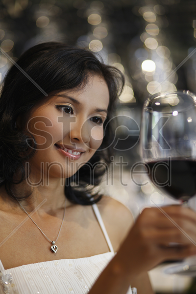 woman looking at glass of red wine stock photo