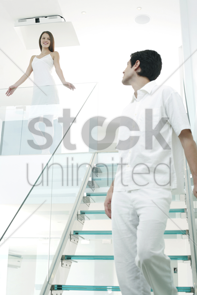 woman looking at her boyfriend walking down the staircase stock photo