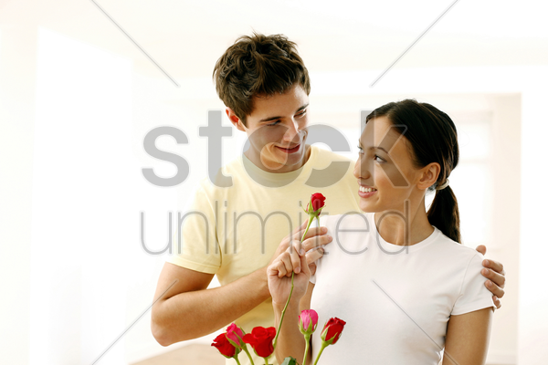 woman looking at her boyfriend while holding a rose stock photo