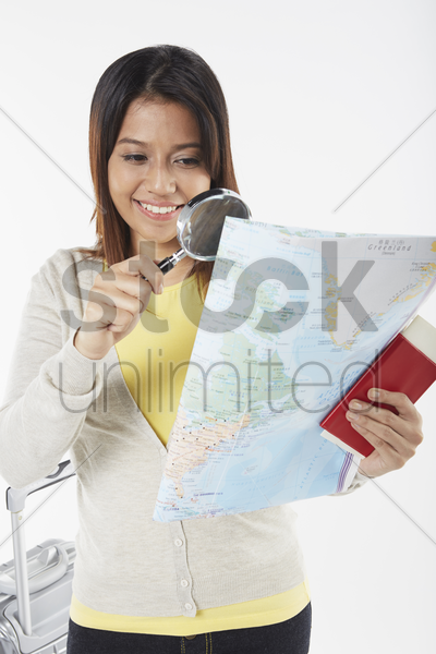 woman looking at map with magnifying glass stock photo