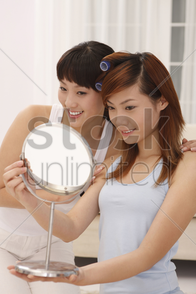 woman looking at mirror after getting her hair curled, friend watching stock photo