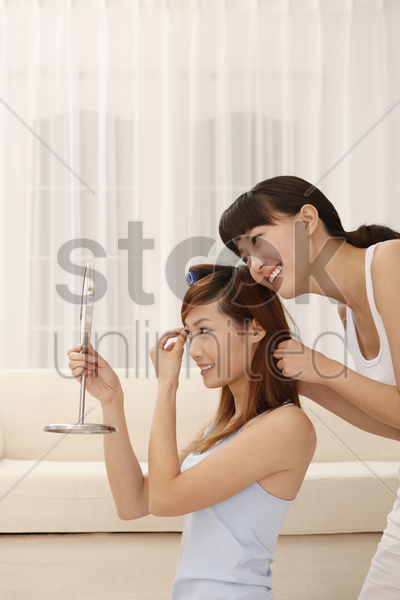 woman looking at mirror while friend curling her hair stock photo