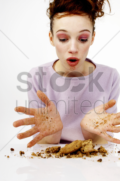 woman looking at the broken cookies stock photo