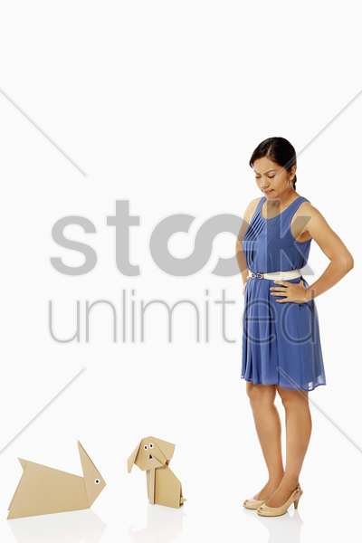 woman looking at the paper dog and paper rabbit, contemplating stock photo