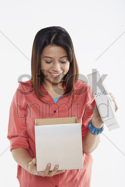 woman looking into opened gift box stock photo