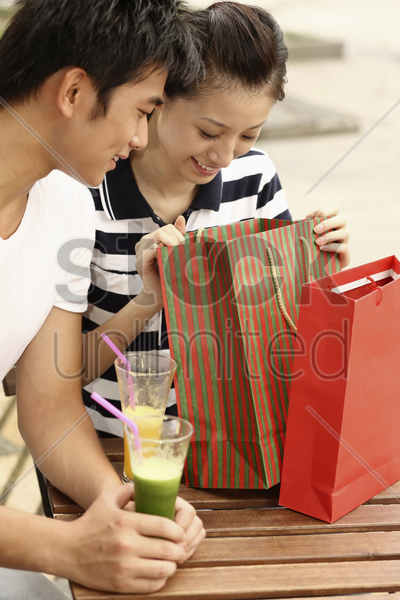 woman looking into paperbag, man watching stock photo