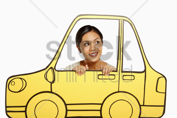 woman looking out of a cardboard car window stock photo