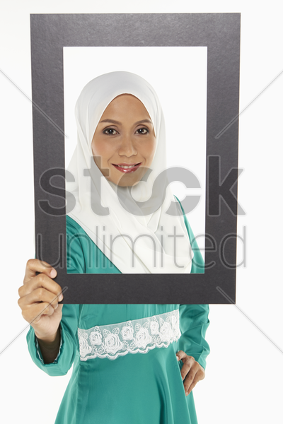 woman looking through a cut out frame stock photo