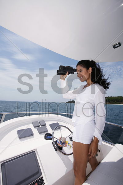 woman looking through binoculars on yacht stock photo