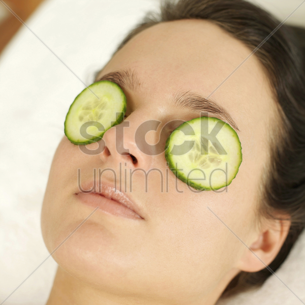 woman lying down with sliced cucumbers covering her eyes stock photo