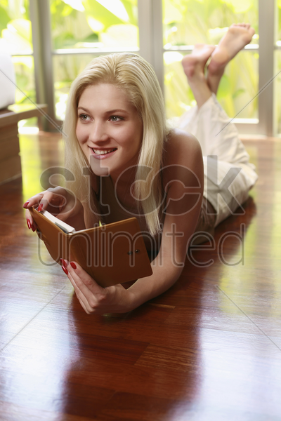 woman lying forward holding an organizer with her legs up stock photo