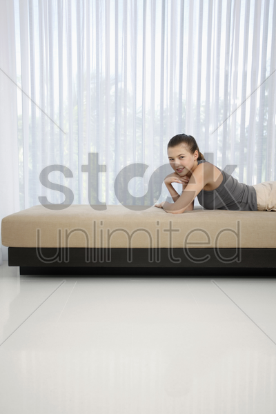 woman lying forward on sofa stock photo