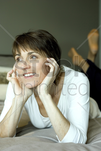 woman lying forward on the bed daydreaming stock photo