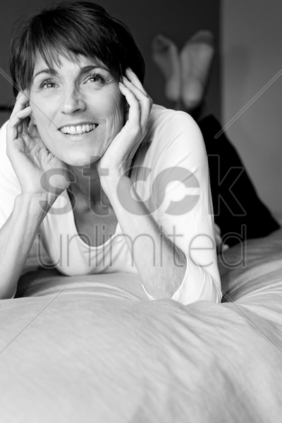 woman lying forward on the bed smiling stock photo