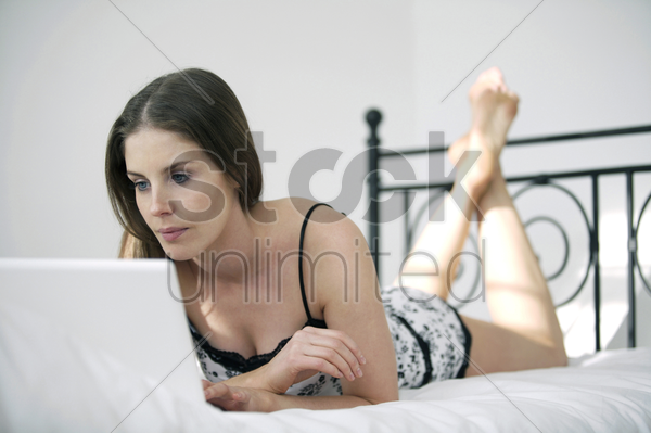 woman lying forward on the bed using laptop stock photo