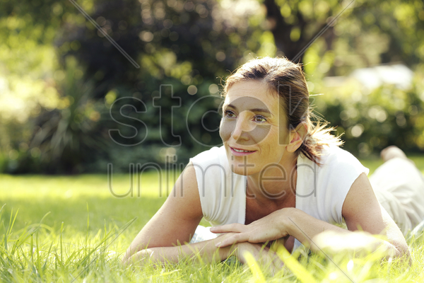 woman lying forward on the field smiling stock photo