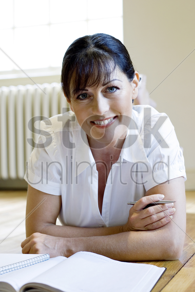 woman lying forward on the floor smiling at the camera stock photo
