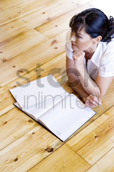 woman lying forward on the floor thinking stock photo