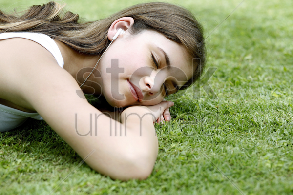 woman lying forward on the grass listening to music stock photo
