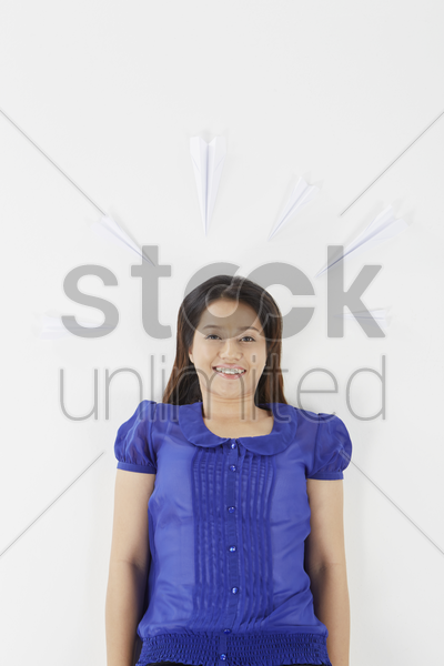 woman lying on back with paper airplanes pointing toward her stock photo