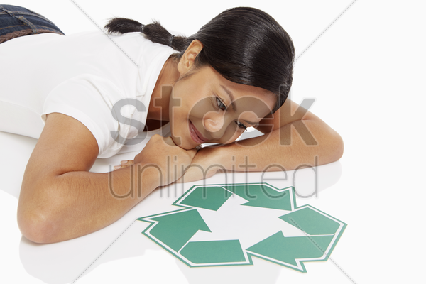 woman lying on front, looking at a recycle logo stock photo