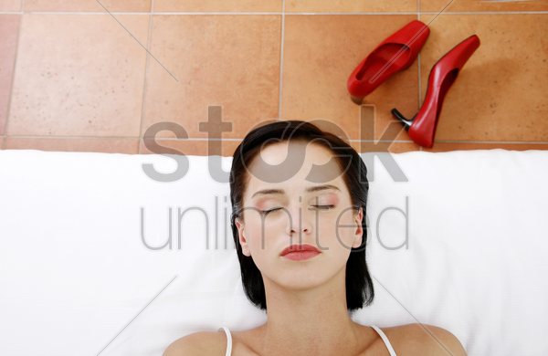 woman lying on the bed with her eyes closed stock photo