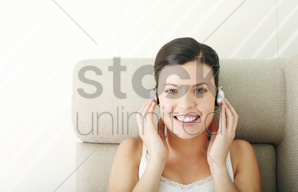 woman lying on the couch listening to music on the headphones stock photo