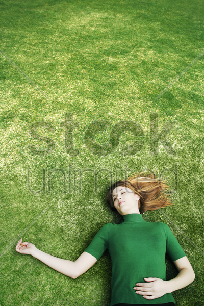 woman lying on the field stock photo