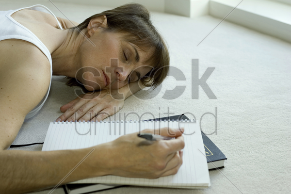woman lying on the floor sleeping with pen in her hand stock photo