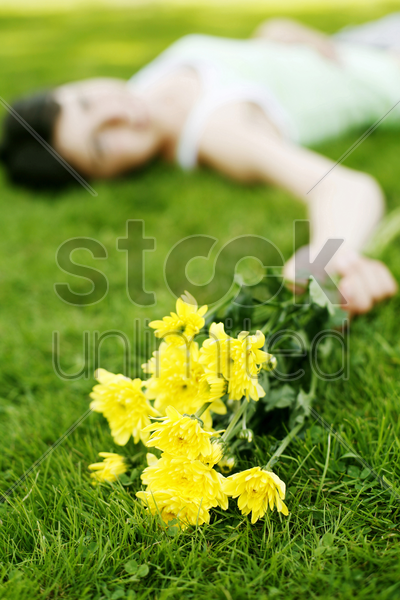 woman lying on the grass holding flowers stock photo