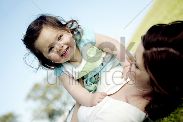 woman lying on the grass holding her daughter stock photo