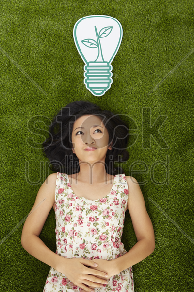 woman lying on the grass, smiling stock photo