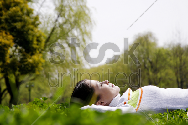 woman lying on the grass stock photo