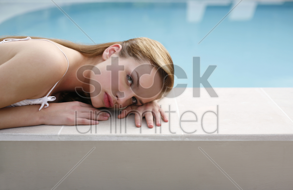 woman lying on the pool side stock photo