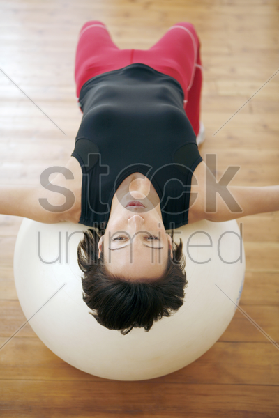 woman lying with her back on fitness ball stock photo