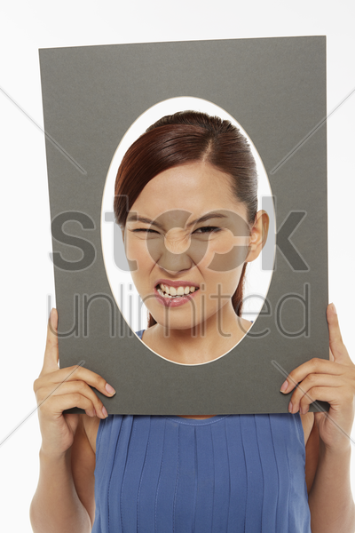 woman making faces at the camera, looking angry stock photo