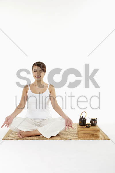 woman meditating with earphones on stock photo