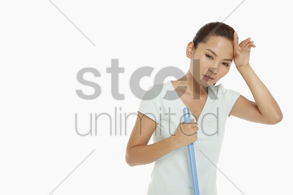 woman mopping the floor and touching her forehead stock photo