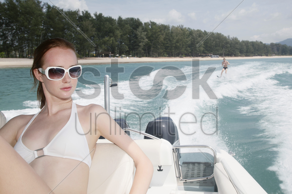 woman on speedboat, man waterskiing in the background stock photo
