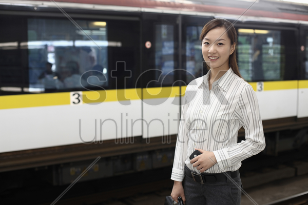 woman on train station platform stock photo